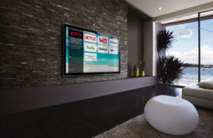 Image of a hotel room by the beach with Enseo's user interface on the TV