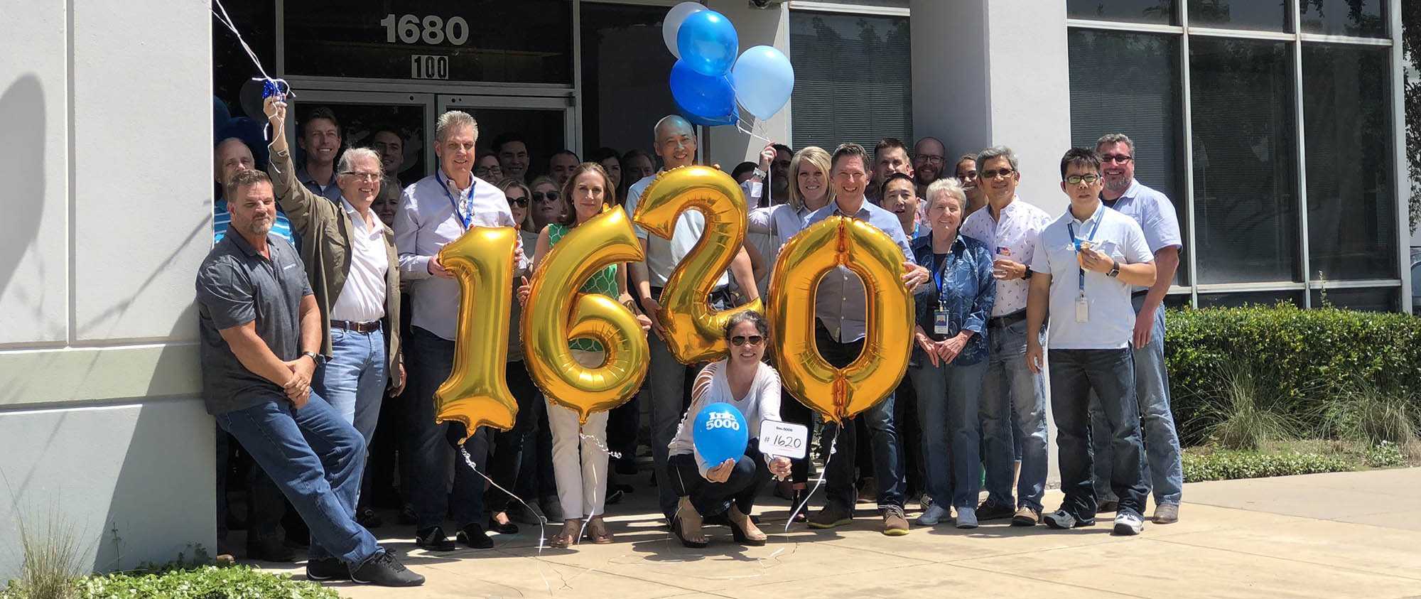 Group picture of Enseo employees holding golden balloon numbers that read 1620 for the Inc 5000