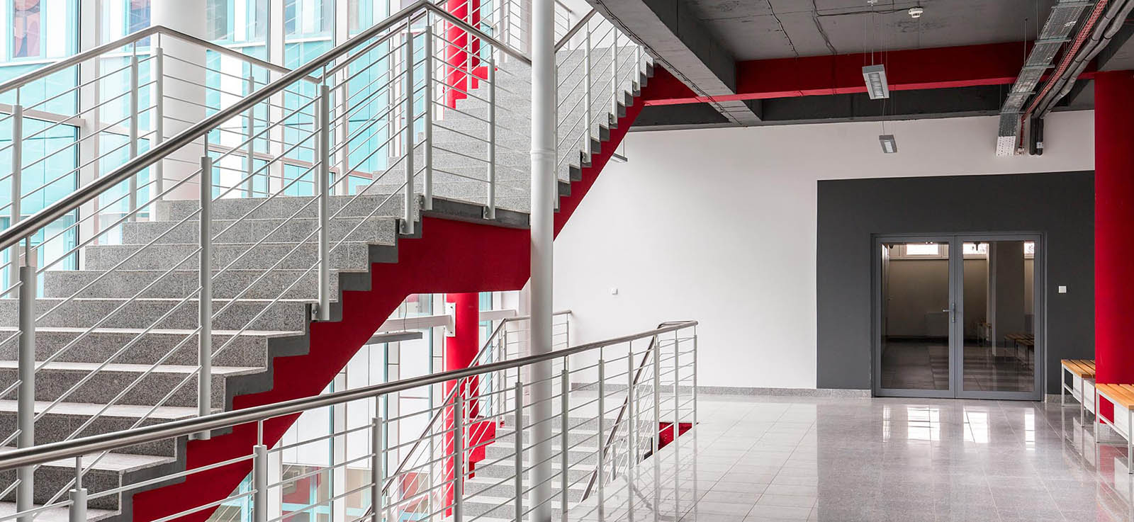 Open, empty school hallway with red, white, and dark grey theme