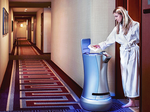 Woman in robe at a hotel retreiving a delivery from a hotel robot
