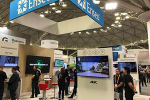 the Enseo booth at HITEC Minneapolis 2019. Several HD and 4K tvs on pillars with displays and many people observing/discussing the technology