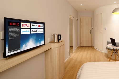 a tv displaying the internet streaming apps of the Enseo platform inside a hotel room