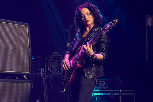 CEO Vanessa Ogle playing electric guitar onstage